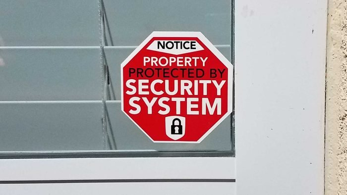 red generic property protected by security system sticker on window