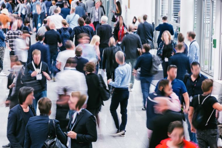 Crowd of anonymous blurred people at a trade show