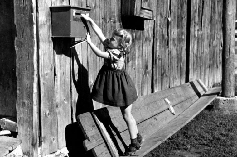 little girl reaching for mailbox