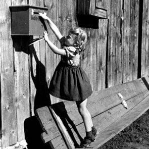 little girl reaching for mailbox