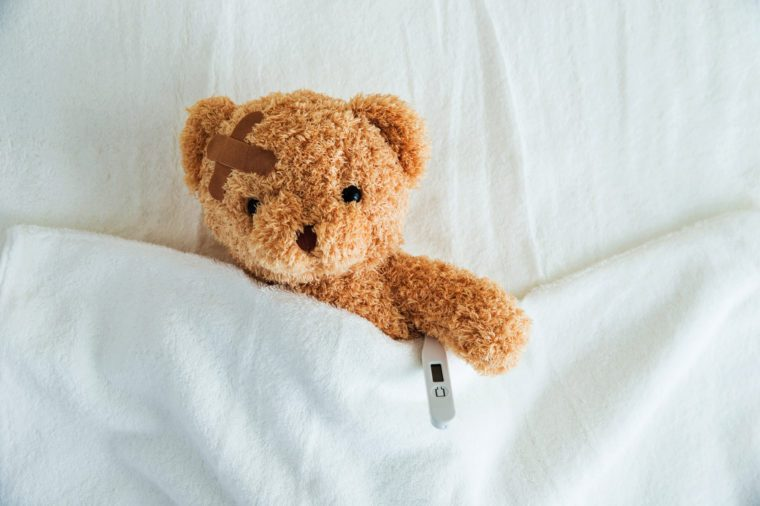 Teddy bear in bed with thermometer and bandage.