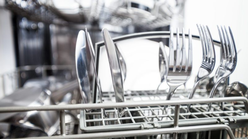 Clean dishes in dishwasher machine after washing, close up
