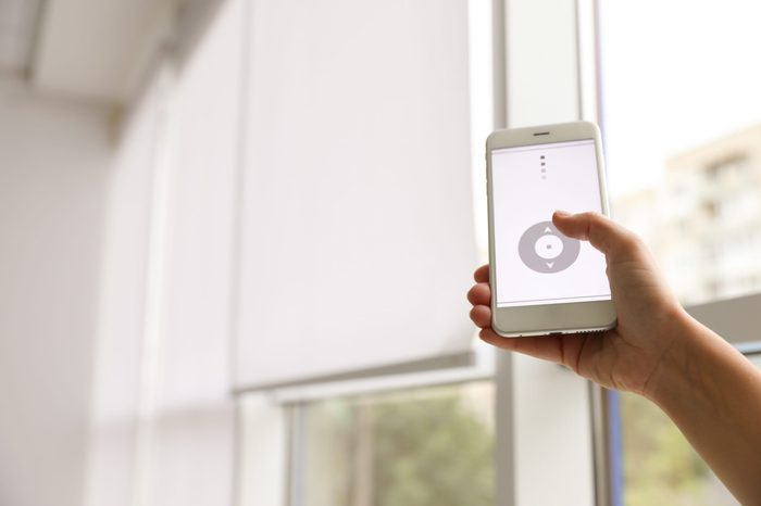 Woman using smart home application on phone to control window blinds indoors, closeup. Space for text