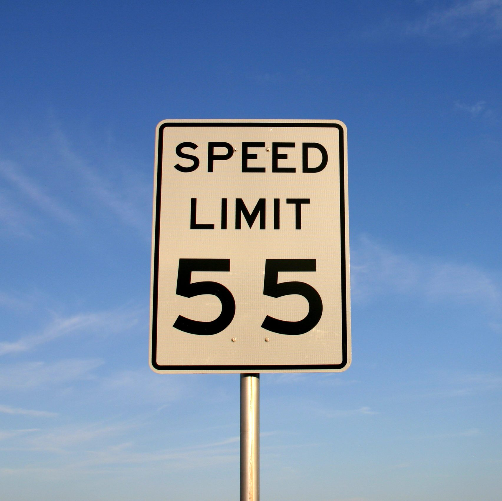 "White sign with ""speed limit 55"" printed in black. Sign is shot against a blue sky. PHOTO ID: SpeedLimit5500016"