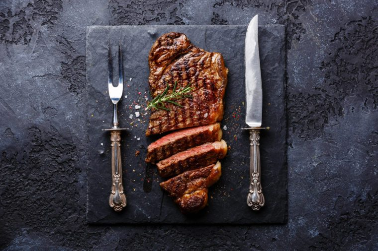 Sliced grilled meat barbecue steak Striploin with knife and fork carving set on black stone slate