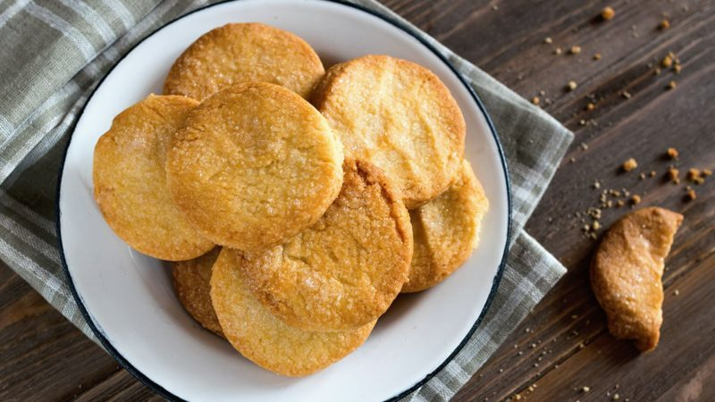 Sugar cookies in a white metal plate on the kitchen table. Wooden background.