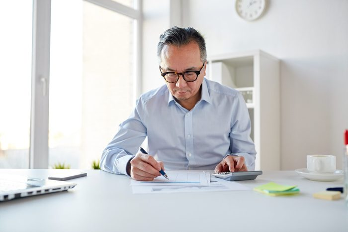 business, people, paperwork and technology concept - businessman with calculator and paper working in office
