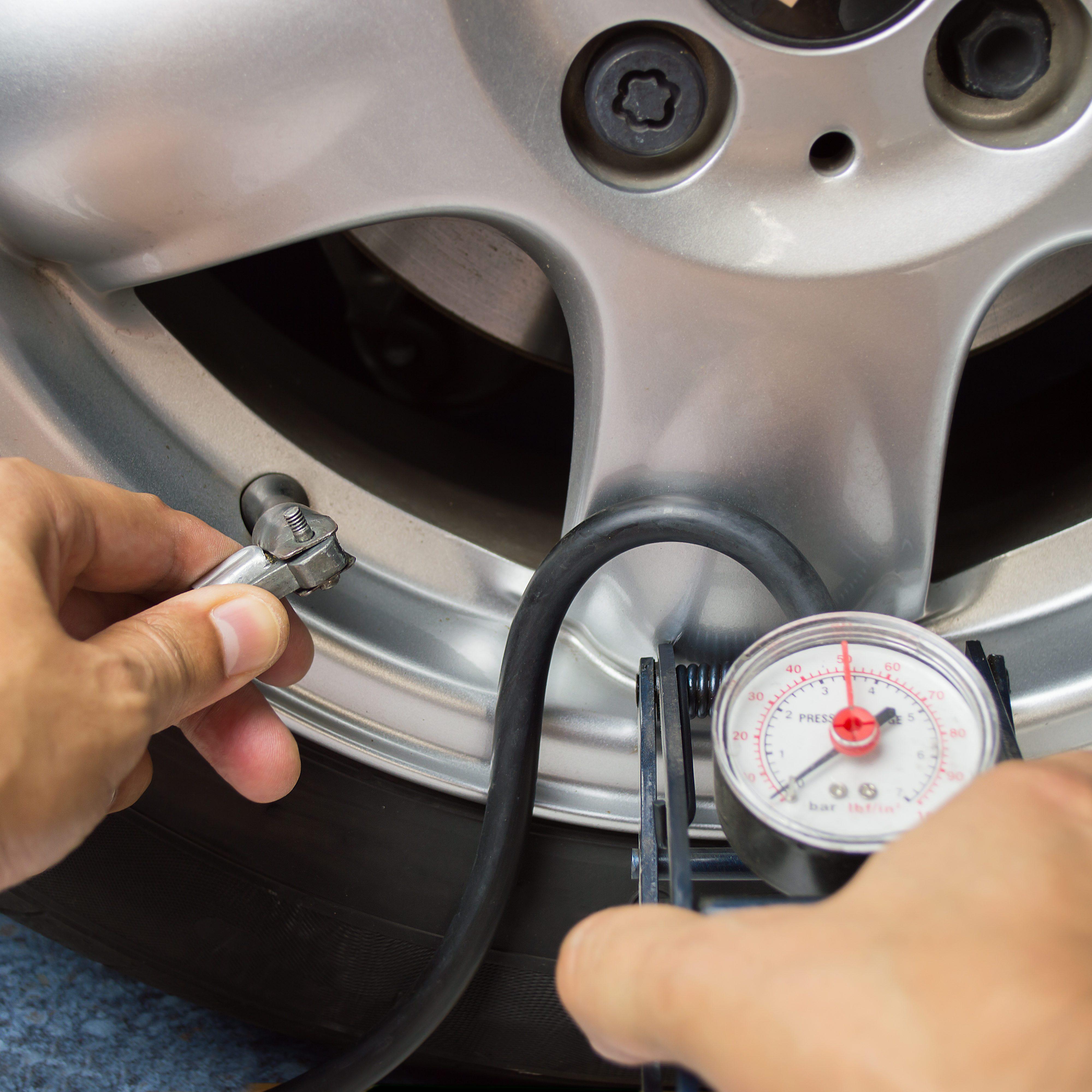 hand and car wheel add air pressure