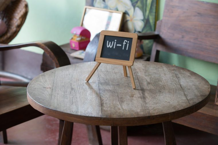 Wifi sign on wood table in public cafe. Natural light.