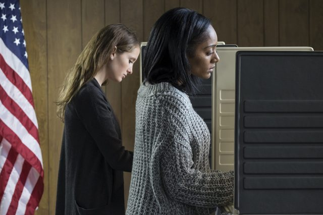 Two young adult women voting in a voting booth