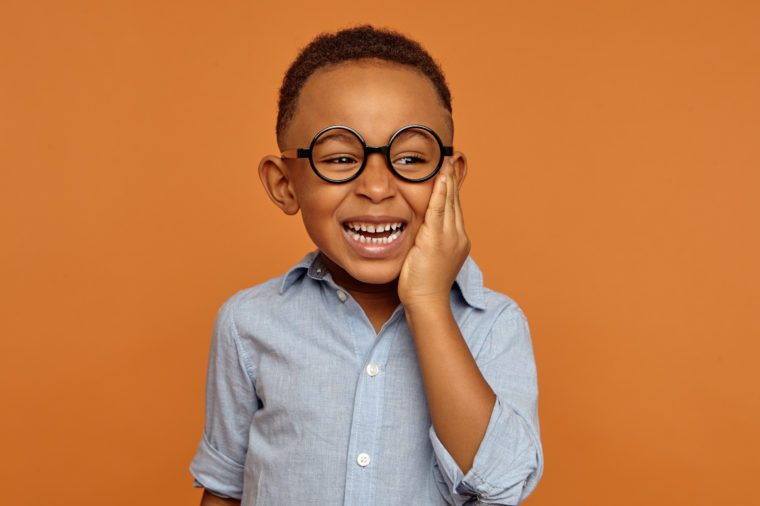 Emotional black dark-skinned little boy grimacing and holding hand on his cheek because of intolerable toothache. Handsome cheerful dark skinned African child in glasses and shirt smiling broadly