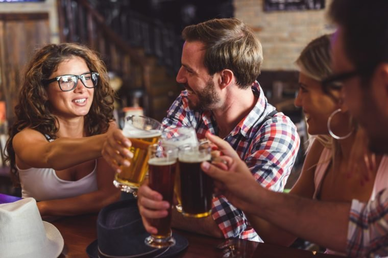 Happy friends having fun at bar - Young trendy people drinking beer and laughing together