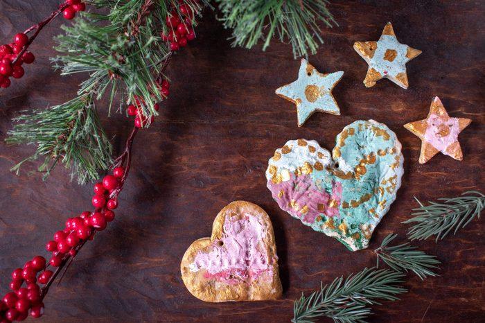 hand painted Christmas salt dough ornaments on festive wood table