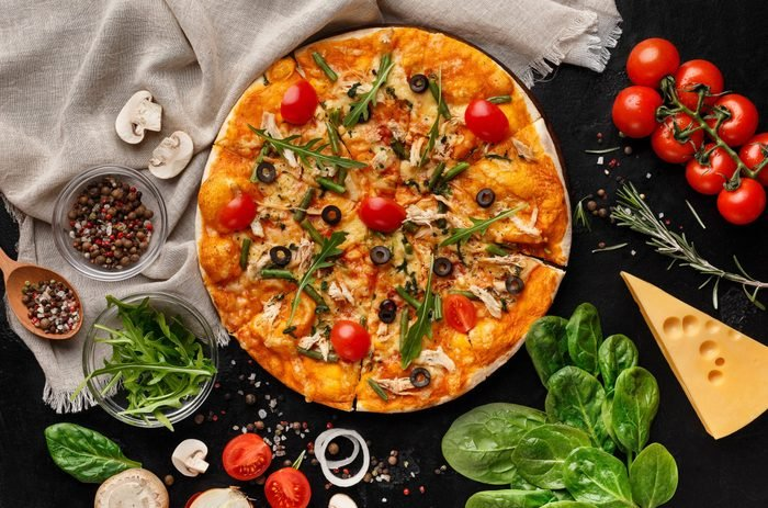 Pizza with rocket salad and cherry tomatoes on table with various ingredients, top view