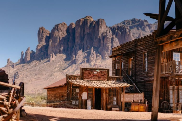 Old Western Wooden Buildings in Goldfield Gold Mine Ghost Town in Youngsberg, Arizona, USA surrounded by cactuses