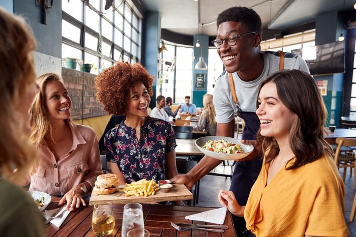 Waiter Serving Group Of Female Friends Meeting For Drinks And Food In Restaurant
