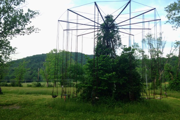 Old carnival ride with swings is overgrown with weeds