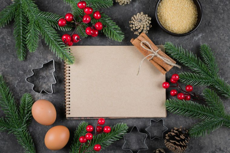 Christmas Recipe Menu Concept. Ingredients for cooking christmas baking and empty white paper notebook on brown stone background. Top view with copy space, mockup concept