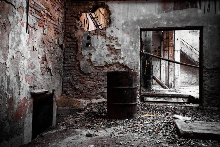 a desolate old industrial building inside, barrel
