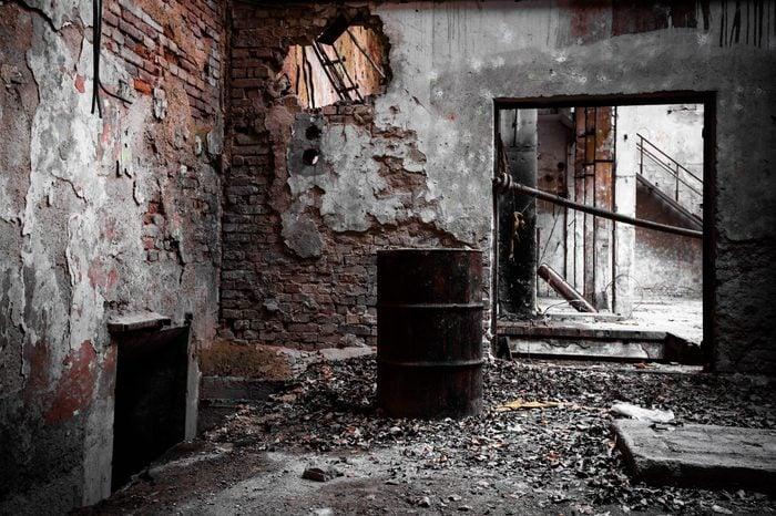 a desolate old industrial building inside, barrel
