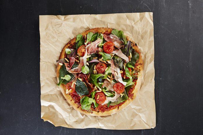 Fresh Italian pizza with ham and salad