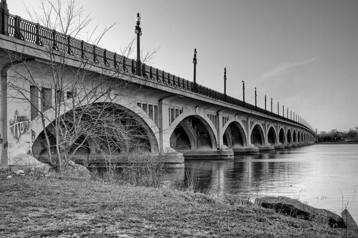 Black and white image of the MacArthur Bridge (once known as the Belle Isle Bridge) at sunset over the Detroit River in Detroit, Michigan.