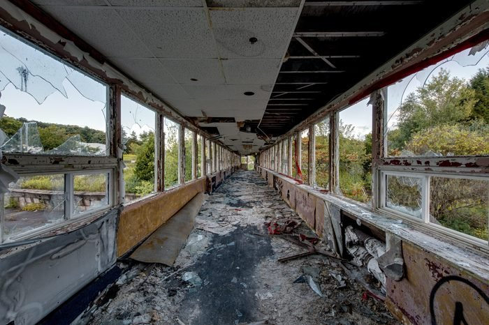 A view of a long and exposed hallway at the decrypt and abandoned Pines Resort in the Catskill Mountains of New York.