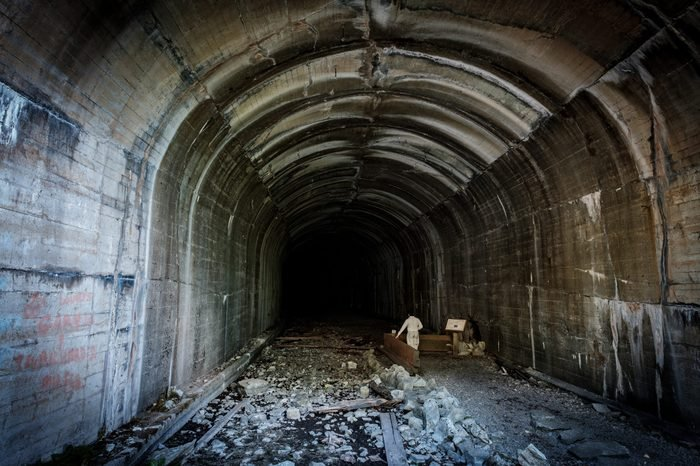 A person stands alone in a very large abandoned train tunnel