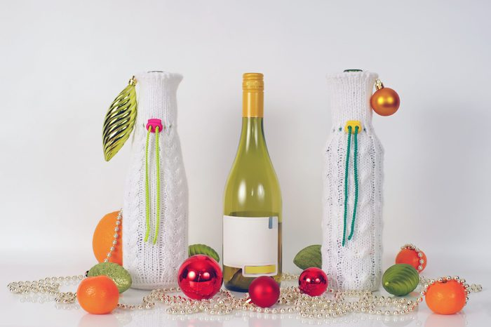 Two white knitted bottle covers and one empty wine bottle placed on a white background