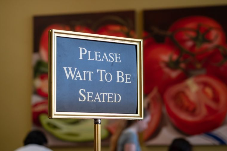 A please wait to be seated sign standing at the front of a restaurant