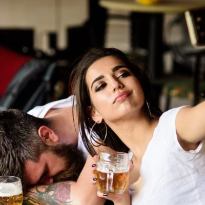 Take selfie to remember great event. Woman making fun of drunk friend. Man drunk fall asleep table and girl with full beer glass. Girl taking selfie photo drunk boyfriend. He appears too weak for her.