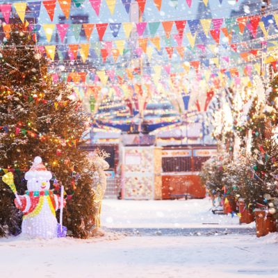 Moscow, Russia. Christmas holidays, winter. Christmas fair on red square. Snowman, colored flags and Christmas tree