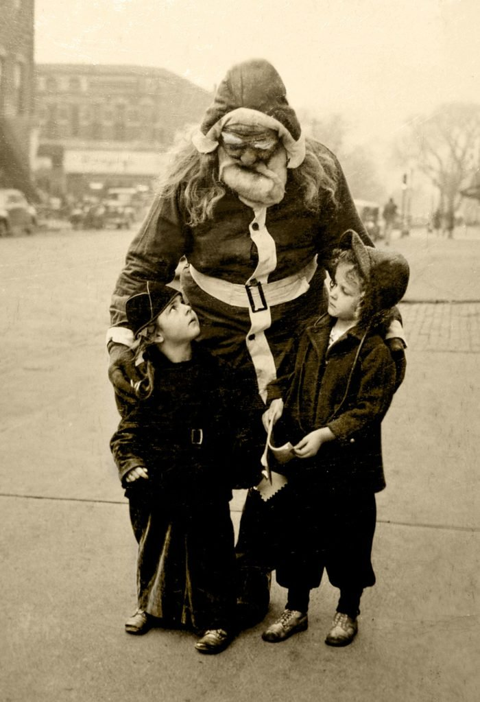 """I am originally from Ottawa, Ill., and my Grandpa Brown used to dress up as Santa and go around the neighbor hood handing out candy to the kids. I found this old photo in my family Bible and thought I would share it. Sorry, I don't know who the two young girls are with Grandpa (Santa) but perhaps someone may remember this and identify who they may be. It must have been taken around 1947-1950 as after that period, my family moved to California. The photo was in the local newspaper along with a short written piece. My Grandpa Brown was a business man in the 30's and 40's in Ottawa. The article went like this: """"Santa Claus has made his last round in the Northwest section of Ottawa but the small frys of the District are confident that someone will replace him and his manner will be as jolly, his supply of candy as ample and his handshake as hearty as that of the Santa Claus who will not be on hand again this year. The real Santa Claus in this area was Edward D. Brown, a big man with a heart to match. He died this past month. For 20 years come Christmas, Brown found funds to buy candy for the small ones of the area, put on his suit and go north on his rounds. He was a neighborhood tradition."""