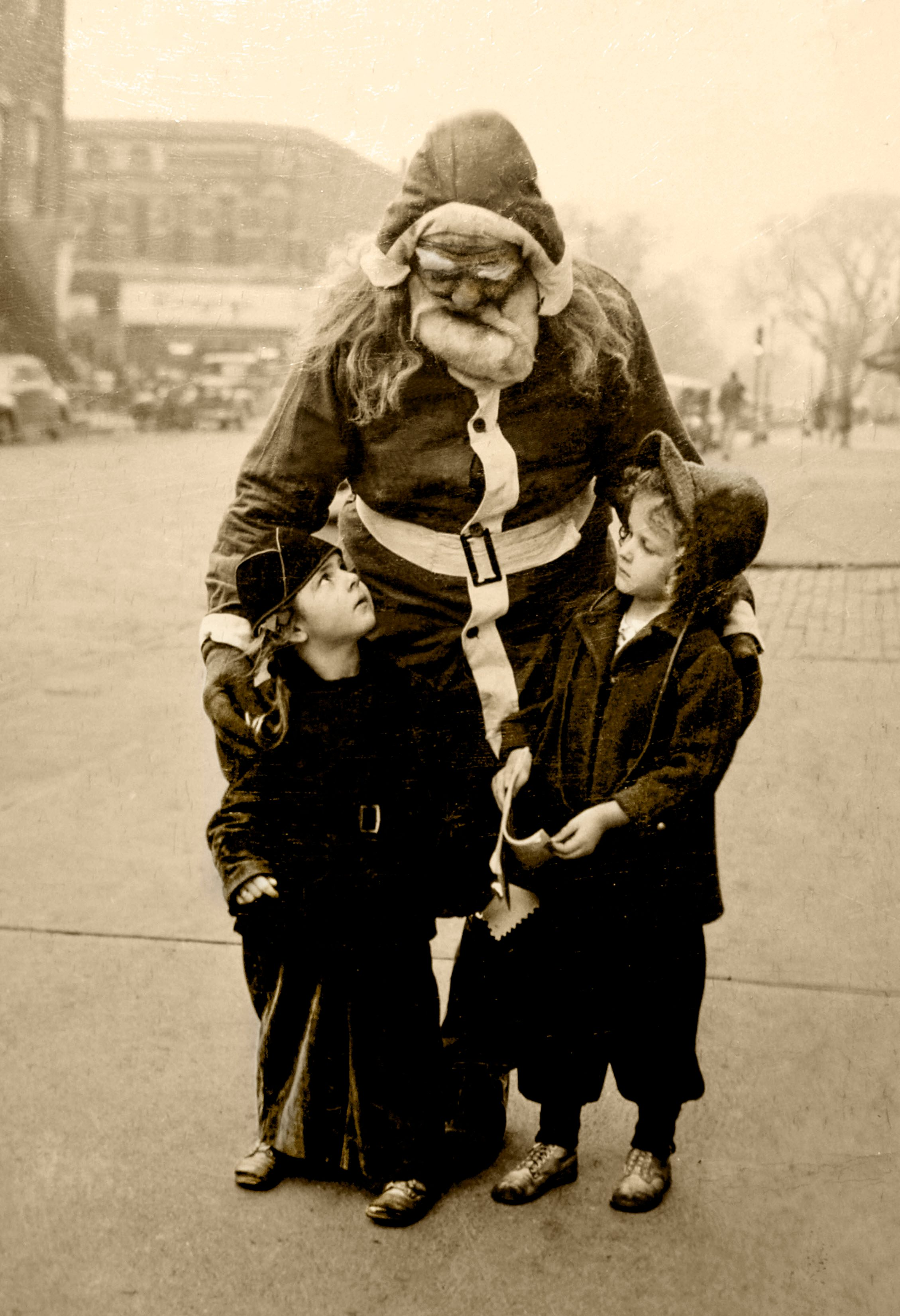 "I am originally from Ottawa, Ill., and my Grandpa Brown used to dress up as Santa and go around the neighbor hood handing out candy to the kids. I found this old photo in my family Bible and thought I would share it. Sorry, I don't know who the two young girls are with Grandpa (Santa) but perhaps someone may remember this and identify who they may be. It must have been taken around 1947-1950 as after that period, my family moved to California. The photo was in the local newspaper along with a short written piece. My Grandpa Brown was a business man in the 30's and 40's in Ottawa. The article went like this: ""Santa Claus has made his last round in the Northwest section of Ottawa but the small frys of the District are confident that someone will replace him and his manner will be as jolly, his supply of candy as ample and his handshake as hearty as that of the Santa Claus who will not be on hand again this year. The real Santa Claus in this area was Edward D. Brown, a big man with a heart to match. He died this past month. For 20 years come Christmas, Brown found funds to buy candy for the small ones of the area, put on his suit and go north on his rounds. He was a neighborhood tradition."