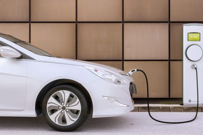 Charging electric car on a city parking lot the future of mobility