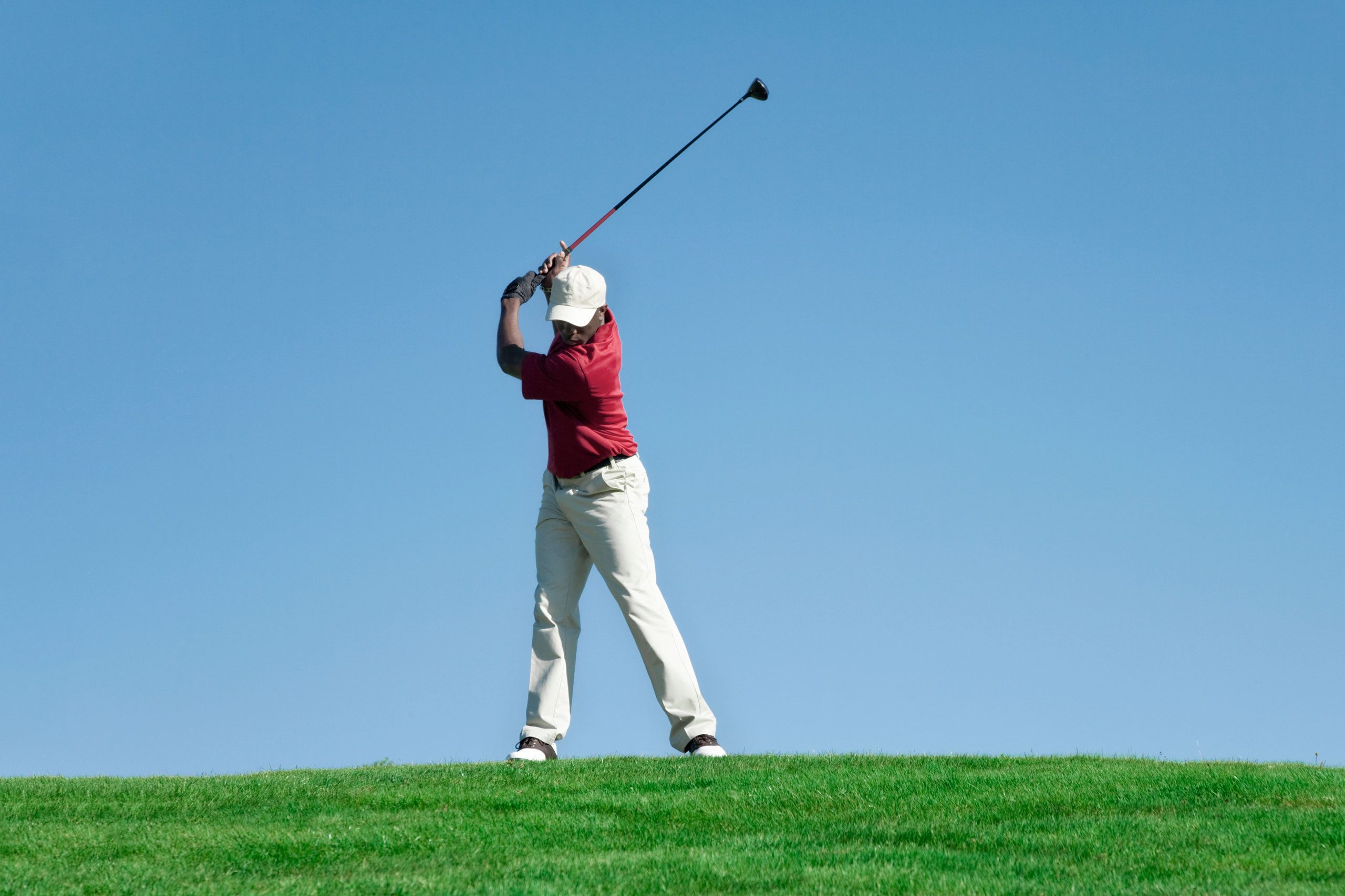 lone golfer stands on the horizon line