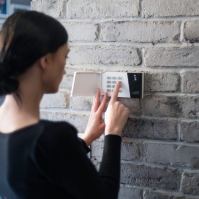 Young woman entering security pin on home alarm keypad. Home security system