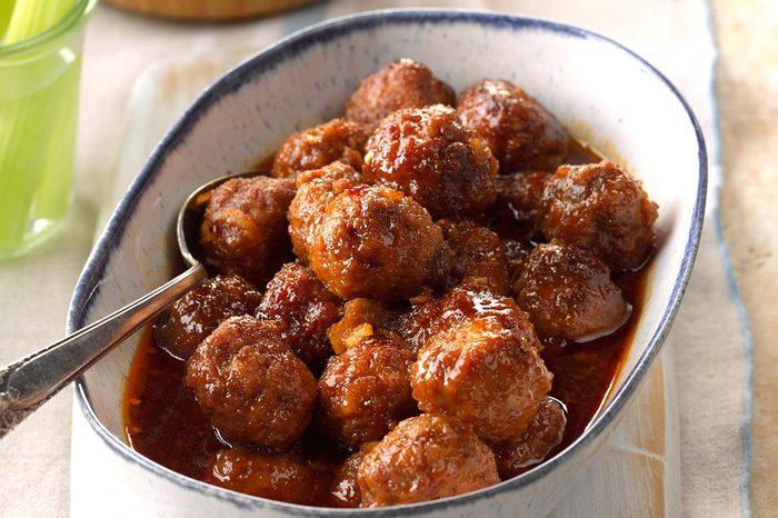 A bowl full of meatballs in honey buffalo sauce