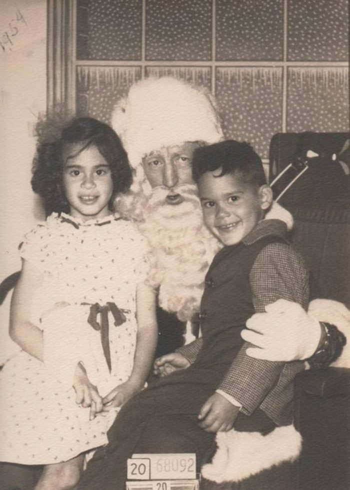 Childhood Christmas experiences are incomplete without a visit to the department store Santa Claus! Here my siblings; Olga and Ruben Garcia; 7 and 5; are all smiles while perched on Santa's lap. The photo was taken in San Francisco; California; in 1954. I was actually already two years old at the time; but was so terrified of Santa that my one and only picture with him was taken when I was eight. After that; I felt I was too old to sit on his lap.