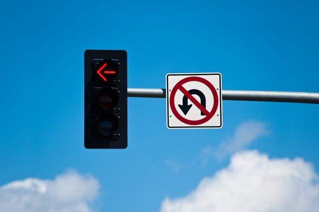 A left turn lane signal light and no u-turn sign.