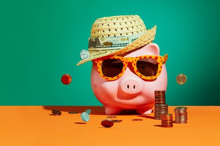 piggy bank in a straw hat and sunglasses surrounded by money concept photograph by Sarah Anne Ward