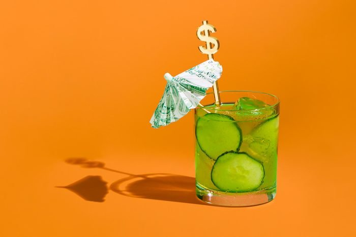Cocktail with money umbrella and stir stick concept photograph by sarah anne ward