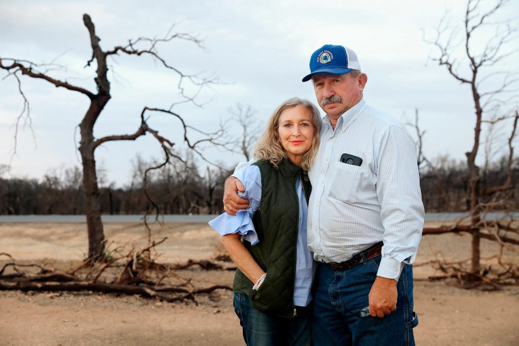 Don Andrews stands with his wife in front of torched trees
