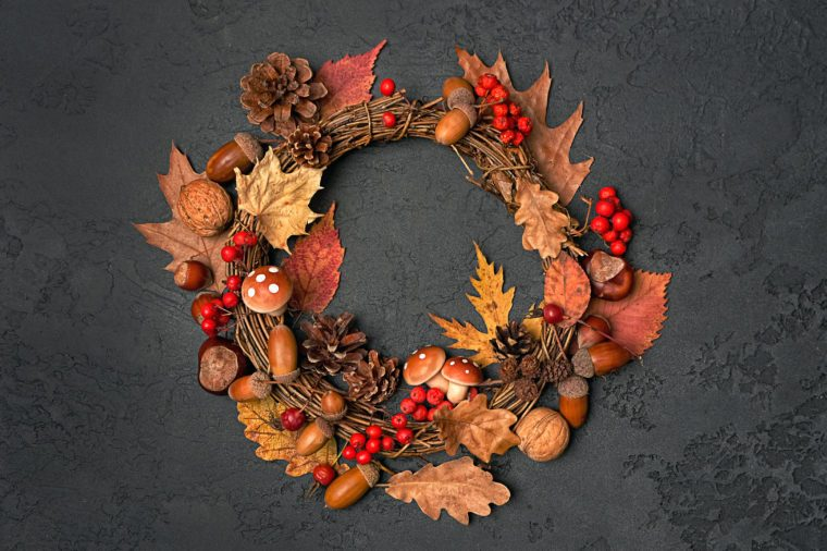 Festive autumn Thanksgiving wreath with mushrooms, fall leaves, red berries, acorns on dark background. autumn holiday, fall, thanksgiving, halloween concept. Flat lay, top view, copy space