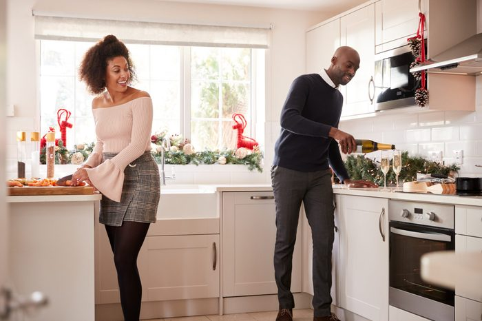 Young mixed race couple preparing Christmas dinner in the kitchen, the man pouring glasses of champagne