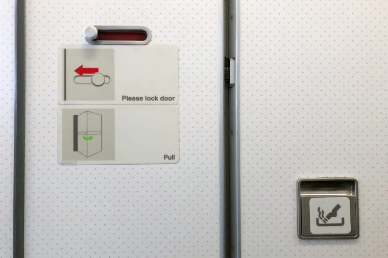 Airplane toilet. How to lock the door. Slide to lock (red color). No smoking. Copy space.
