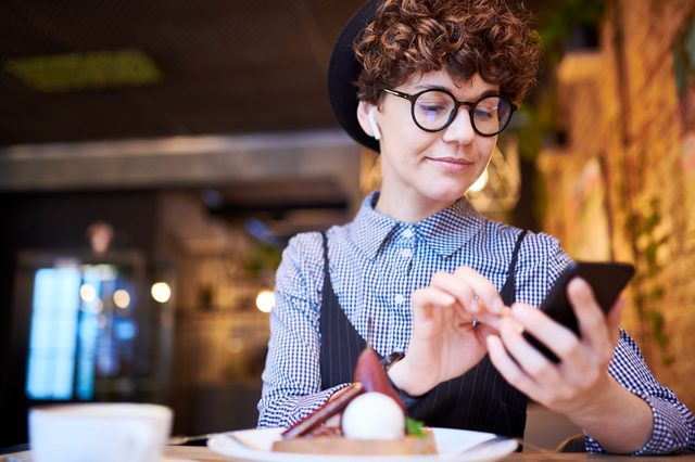 Young woman in eyeglasses and airpods scrolling in her smartphone through playlist while relaxing in cafe