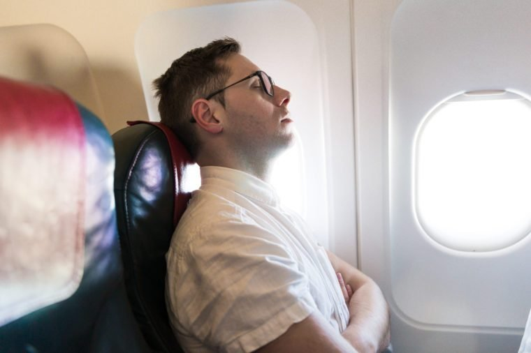 Side view of the elegant young man who is sitting on the plane near the window and sleeping