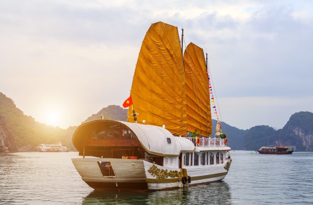 Discover Halong Bay Top Destinations Vietnam view of seascape. Cruise golden Sails liner ship wooden junk sailing rock islands the emerald waters of Ha Long Bay.