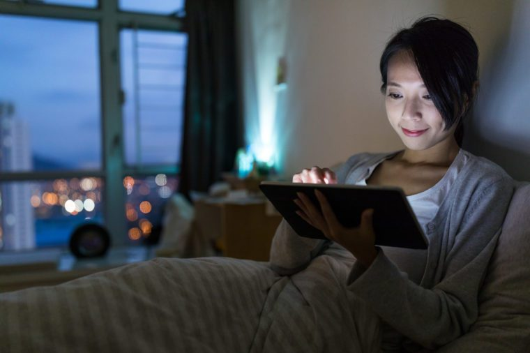 Woman working on digital tablet computer at night